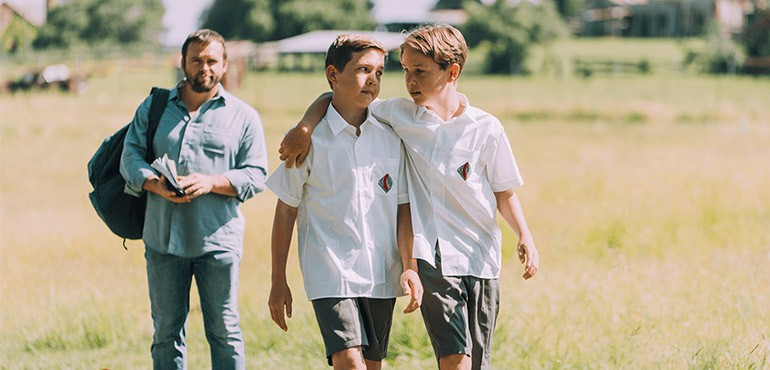 Two teenage boys in school uniform with their father behind them.